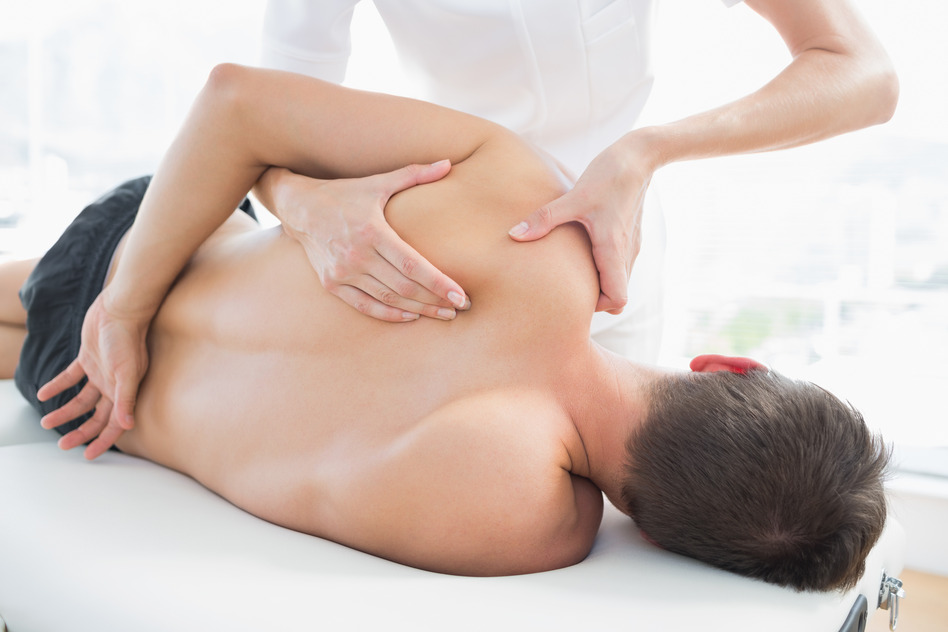 Professional female physiotherapist giving shoulder massage to man in hospital
